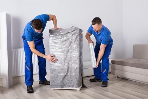 Helden Umzüge - Verpacken von Umzugsgut - Männer verpacken Umzugsgut in Folie